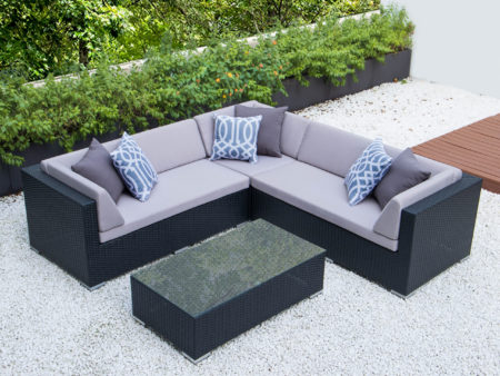 Symmetrical L with glass table and light grey cushions