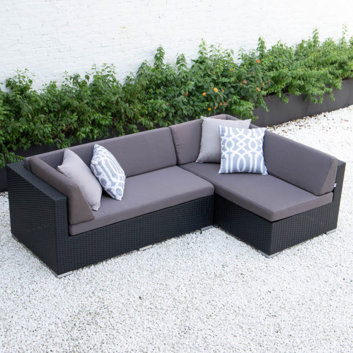 Small L sectional in dark grey cushions